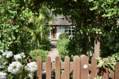 After - Front gate: A picket gate entry through a new wooden arch.