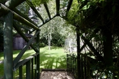 After - Archway through to utility area: An archway and gate provide access to the children's play area, the vegetable garden, greenhouse and shed. This utility area is shielded largely from view from the main garden area and from the house.